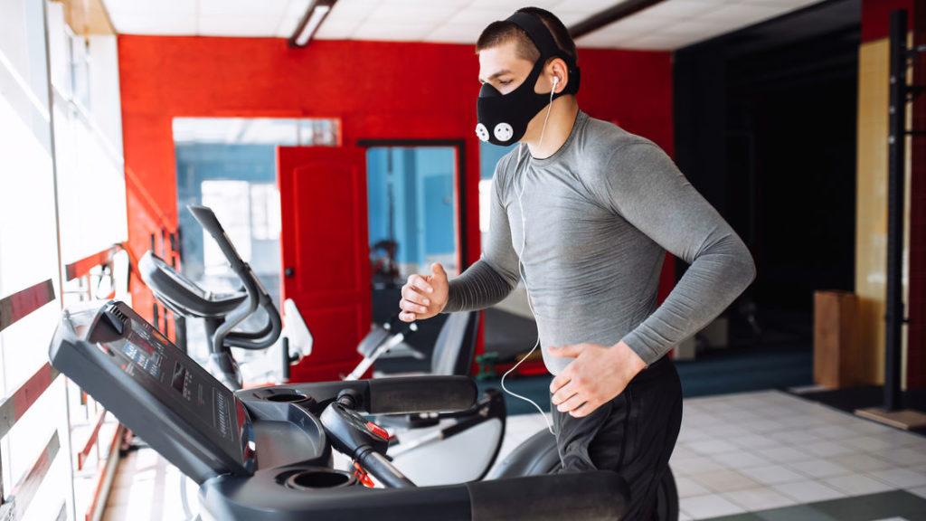 Läufer mit Laufmaske auf Laufband