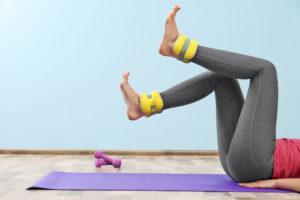 Frau mit Gewichtsmanschetten für Füße