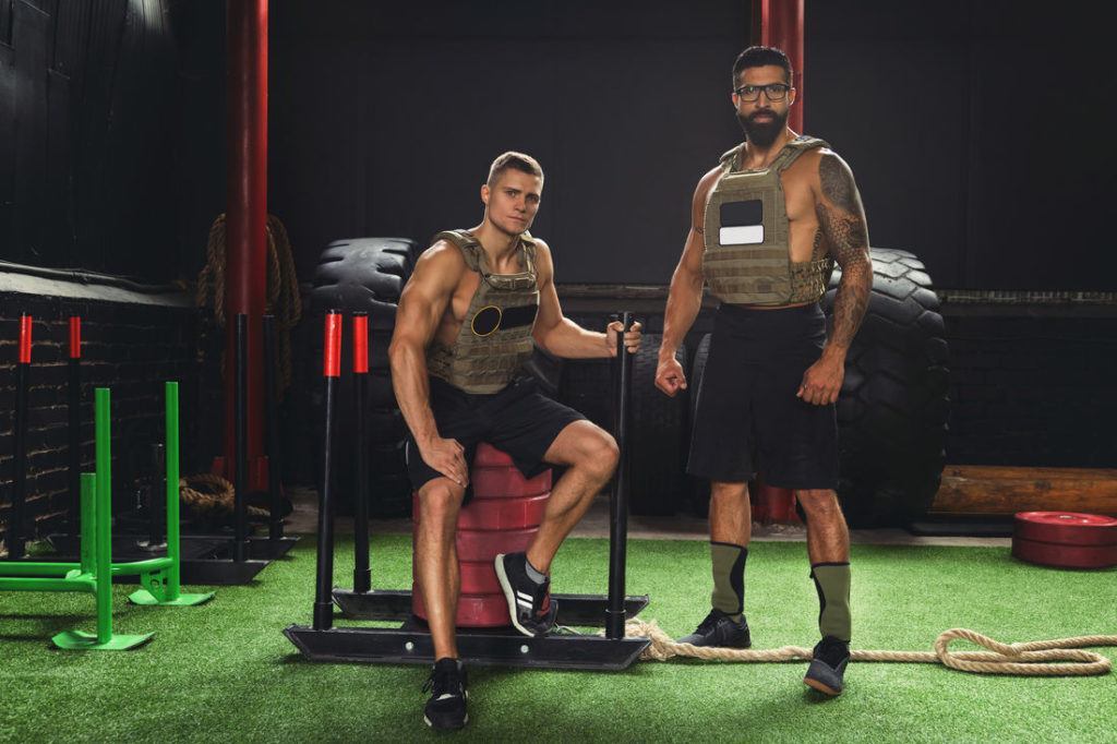 Männer mit Gewichtswesten beim Sport