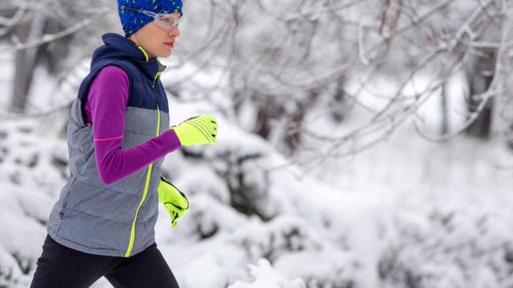 Frau mit Laufhandschuhen läuft im Winter
