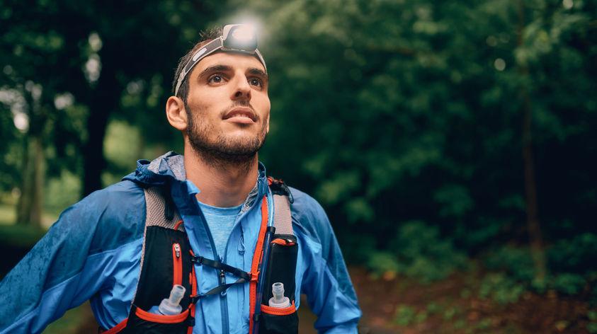 Läufer mit Stirnlampe und Laufrucksack