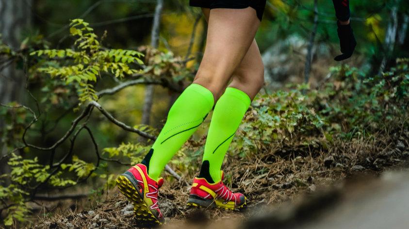 Junge Frau mit Kompressionssocken beim Laufen im Wald